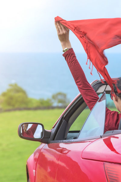 Girl in a red convertible car on background seascape.