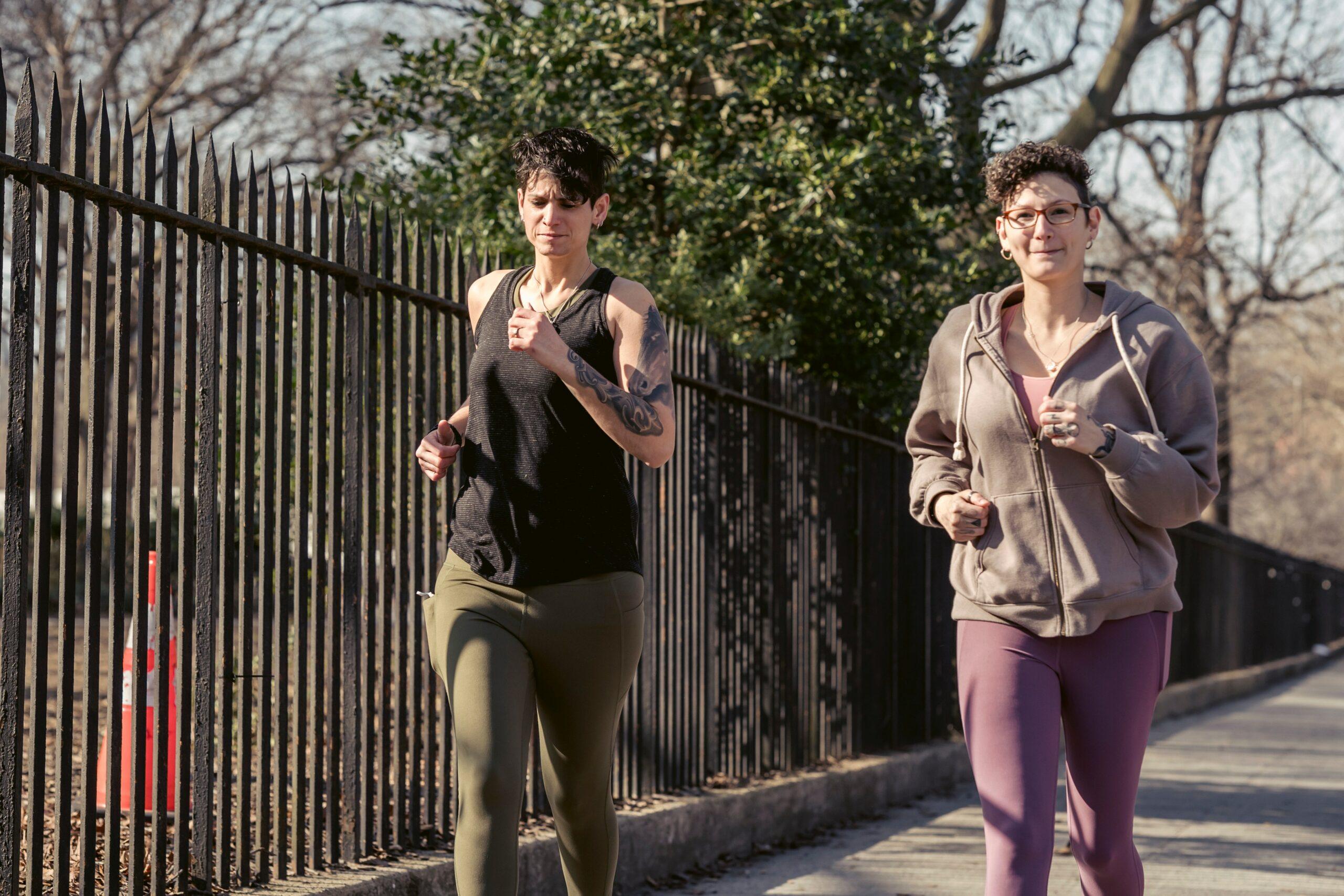 Two women jogging alongside a tall iron fence