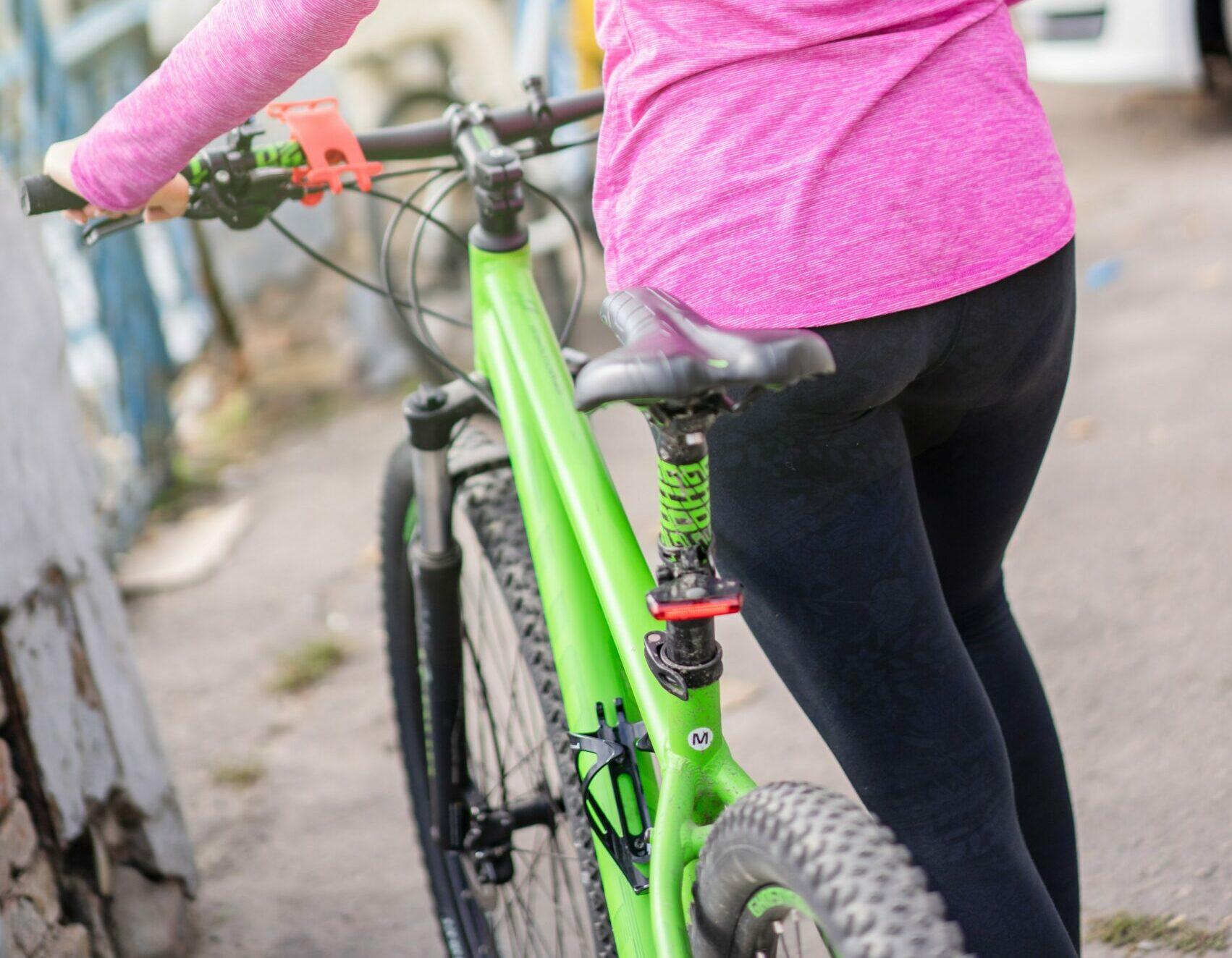 A woman pushing her bike