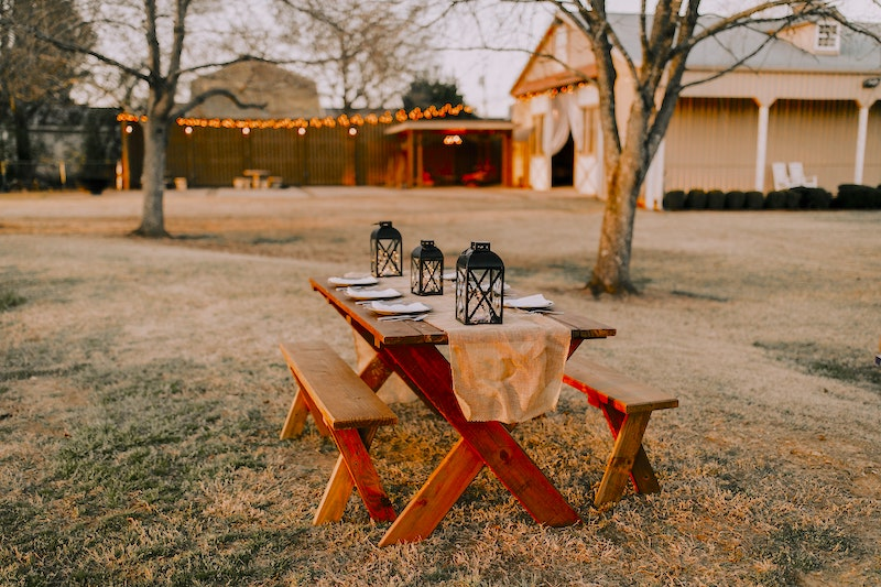 A picnic table outdoors, with dining settings. In front of a house and barn.