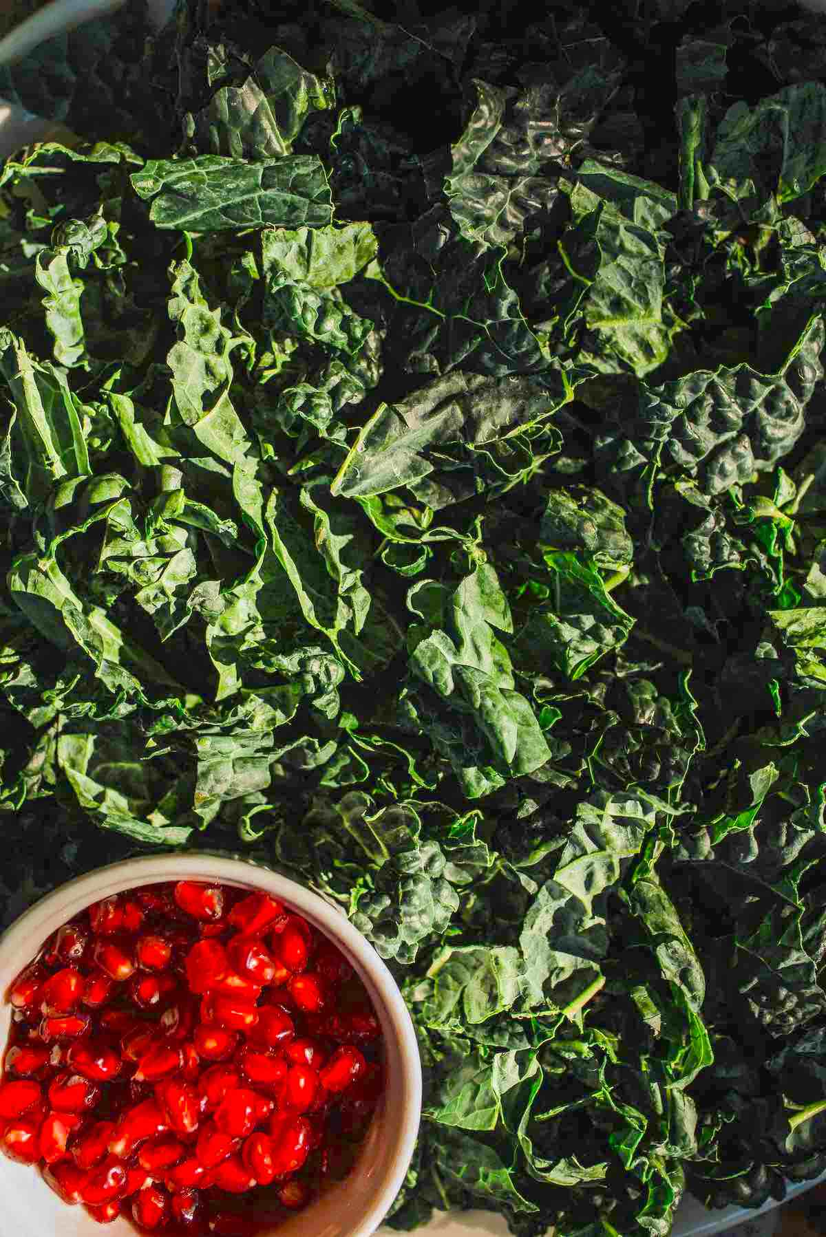 Kale winter greens with a container of pomegranate seeds