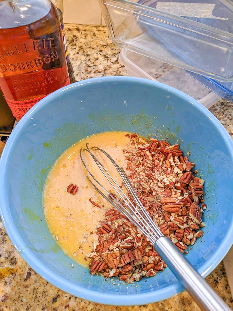 The wet ingredients for the pecan pie and the crushed pecans in a blue mixing bowl