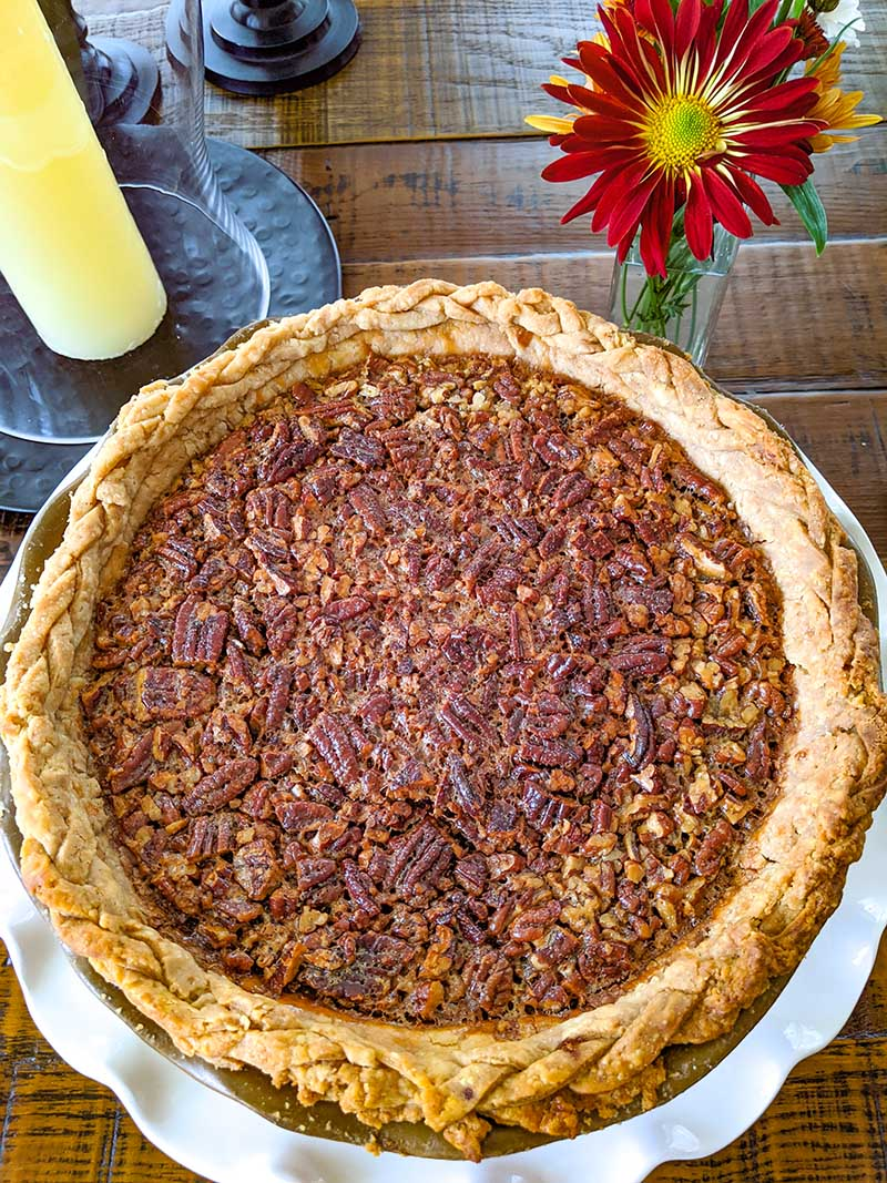 The finished Pecan Pie on a wooden table next to a red flower