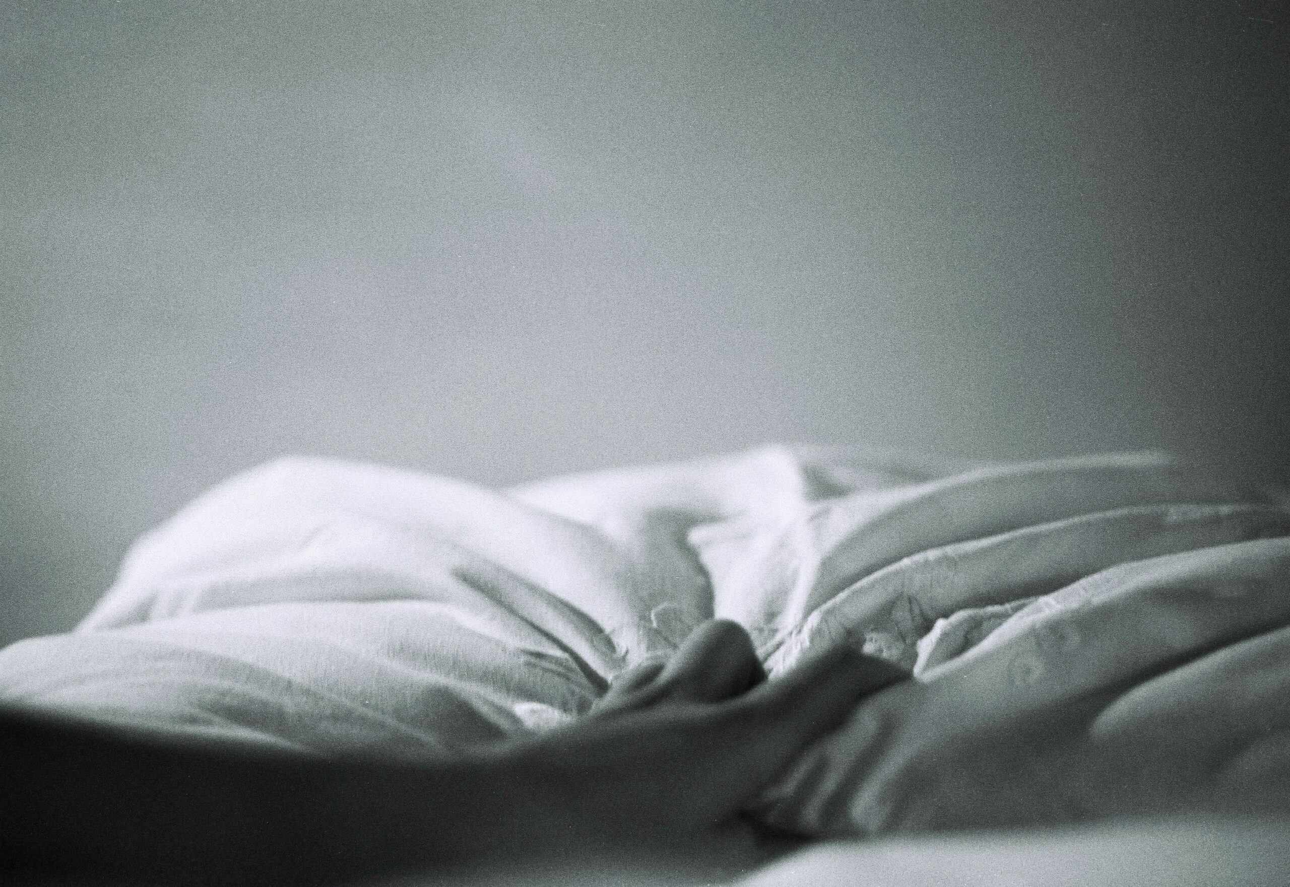 Ruffled bed sheets on an empty bed.