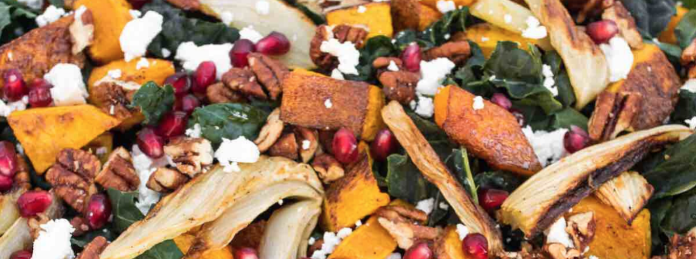 A kale salad with butternut squash, pomegranate seeds, and feta cheese.