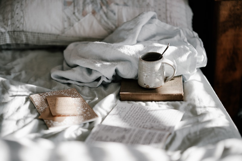 A cozy bed with books and tea