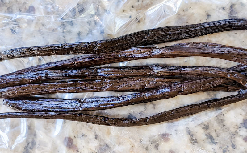 Six strings of vanilla beans sitting on a counter
