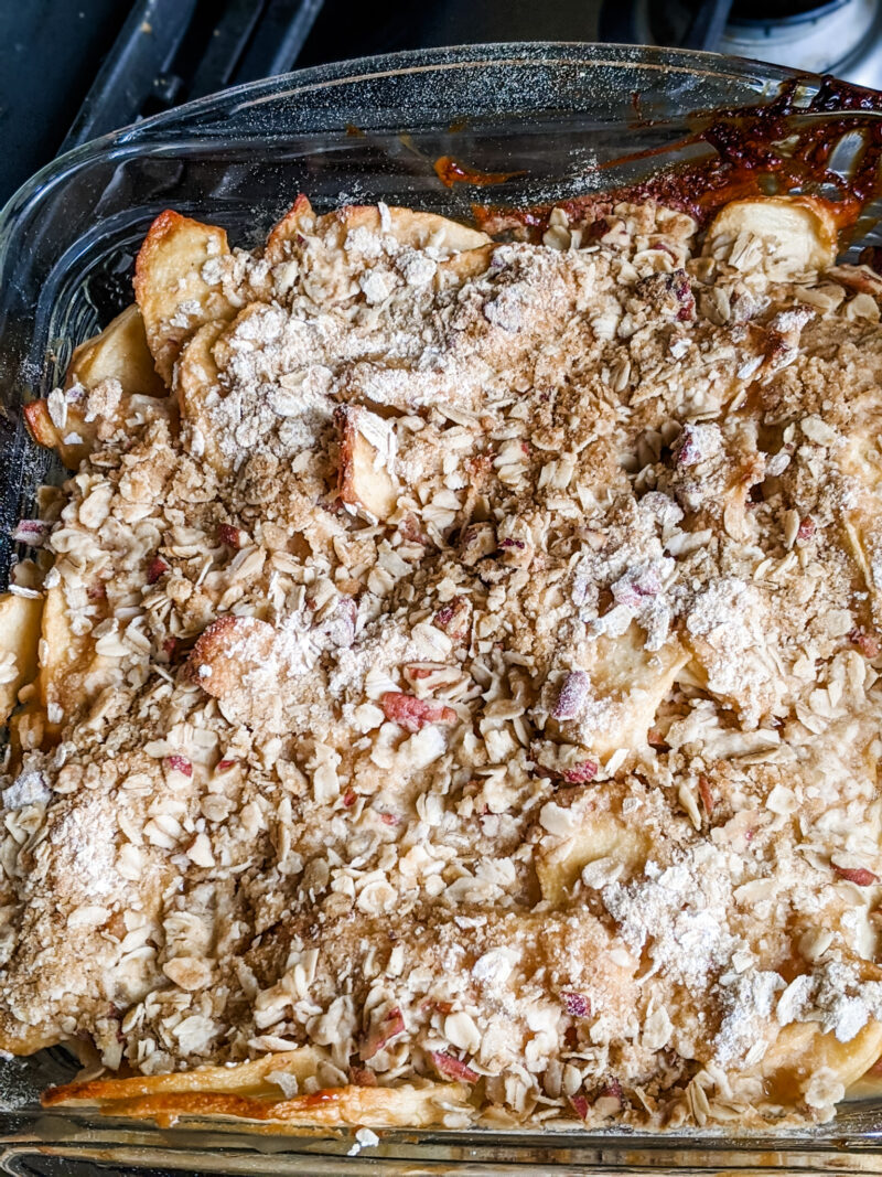 The baked Apple Crisp Recipe in a glass baking dish atop a stove - all baked in one pan for an easy fall recipe