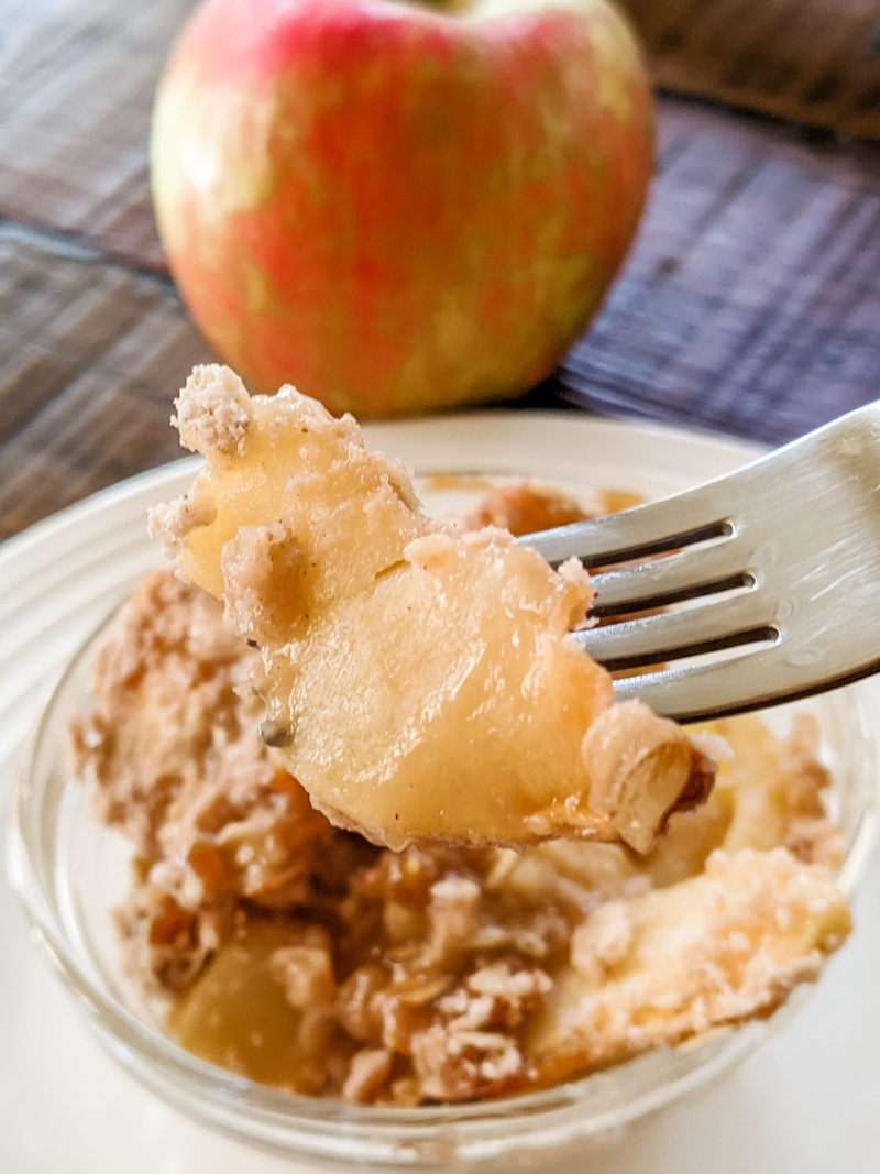 A fork holding up a piece of the finished Apple Crisp with an apple in the background