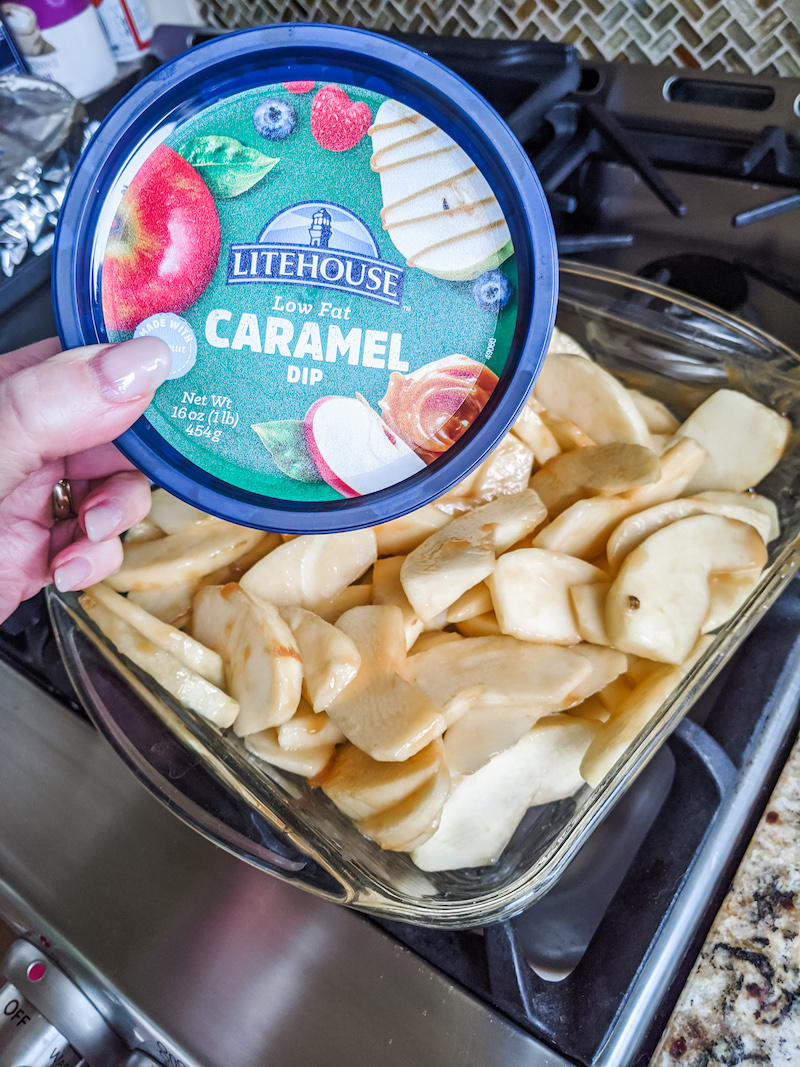 The container of Low fate caramel dip held above the pre-baked Healthy Apple Crisp Recipe