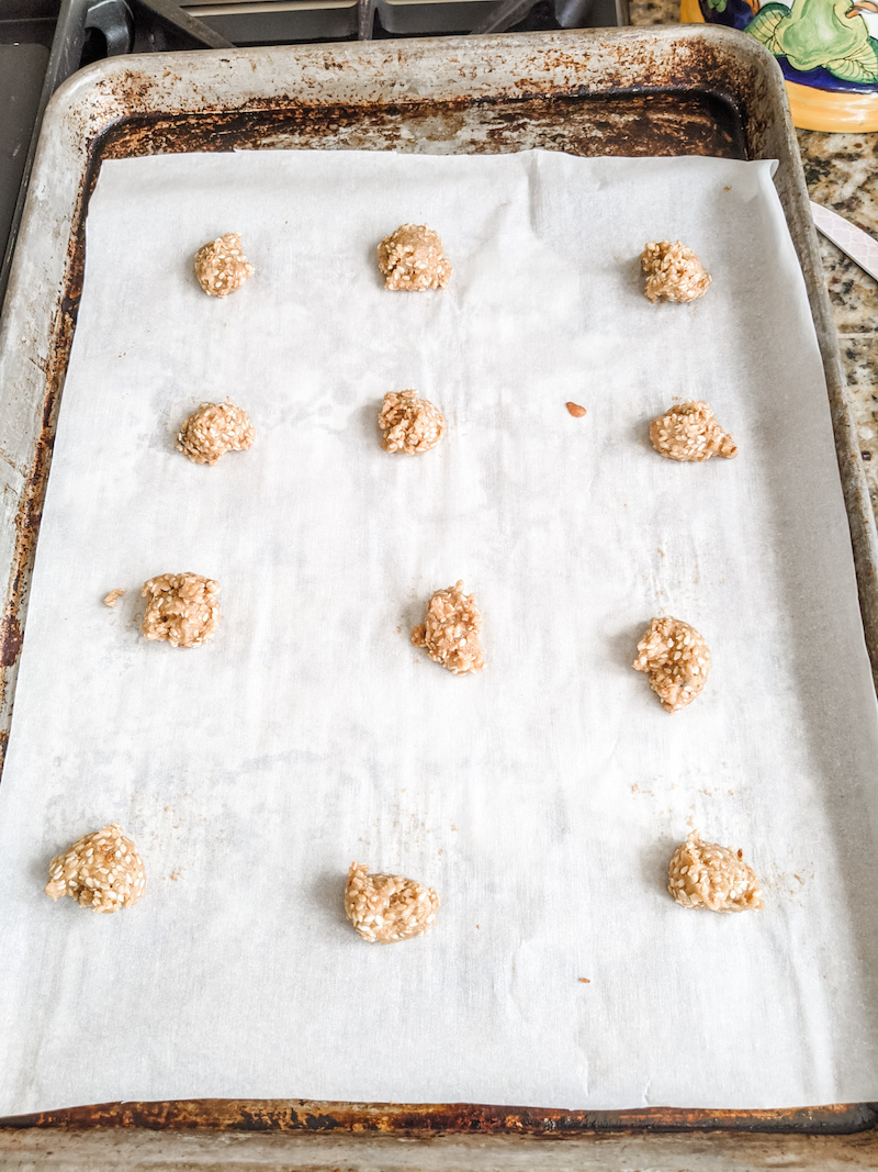 A dozen teaspoon-sized balls of benne wafer batter sitting on a tray lined with parchment paper