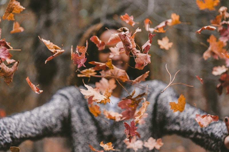 A woman in a sweater throwing leaves in the air