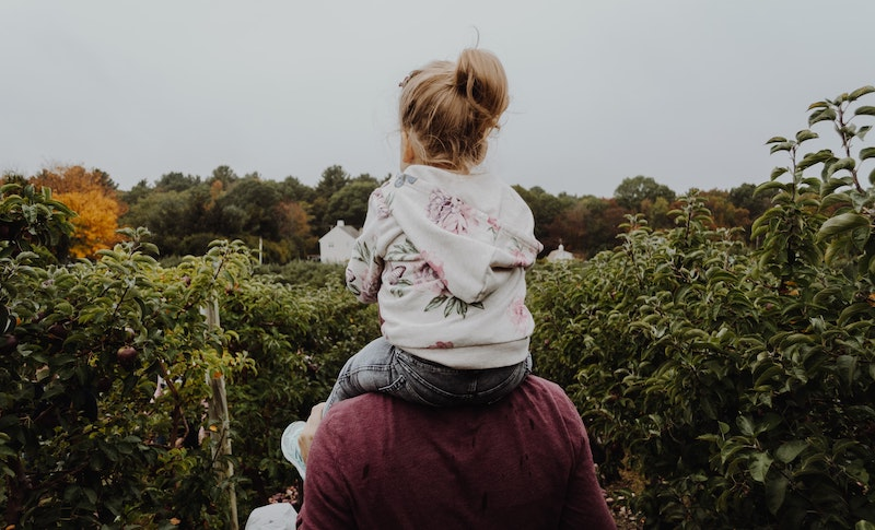 A man with his daughter on his shoulders, walking through a pumpkin patch