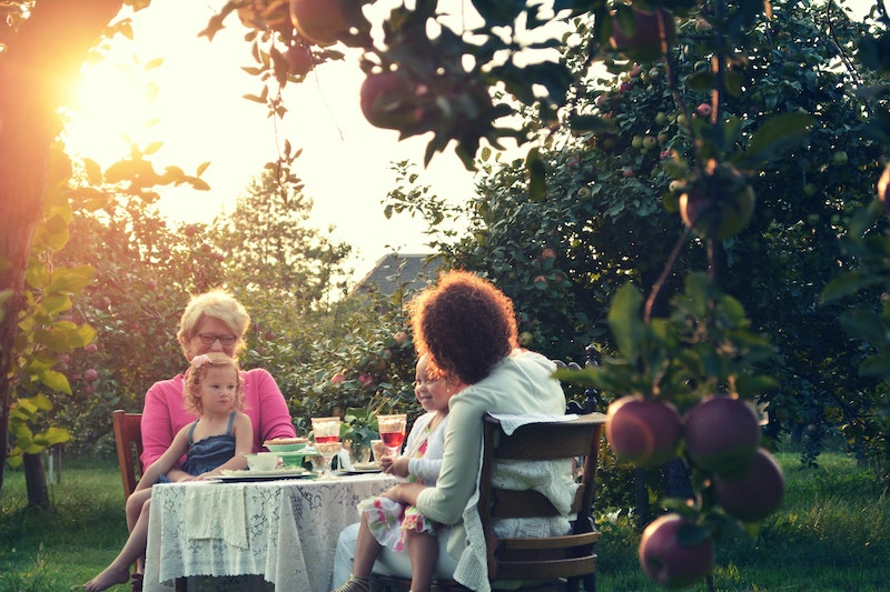 Two women with their granddaughters in their laps, sitting in an orchard with wine and food.