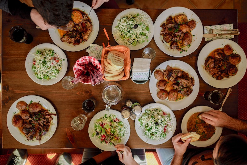 A fall activity of a feast - a table with several autumn dishes and folks eating