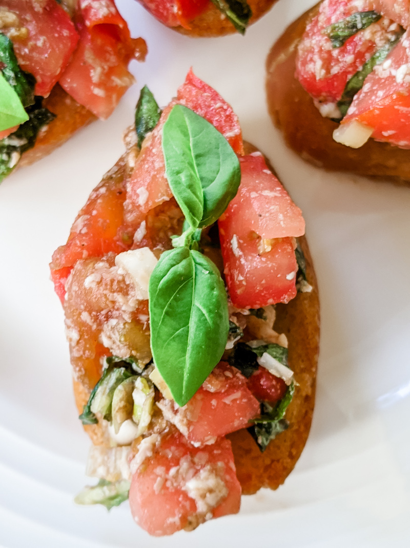 A piece of my easy tomato bruschetta topped with basil