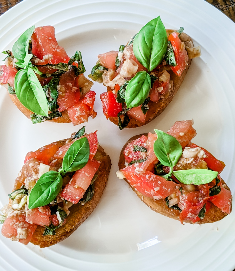 Four finished pieces of my easy tomato bruschetta sitting on a plate