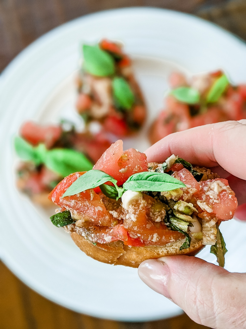 A hand holding a piece of the easy tomato bruschetta with more sitting on a plate in the background