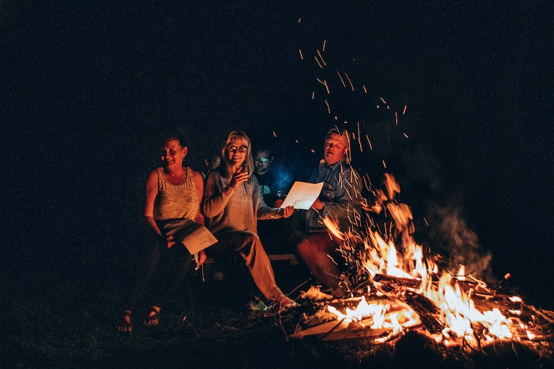 Two women and a man enjoying a fall activity of a bonfire and singing