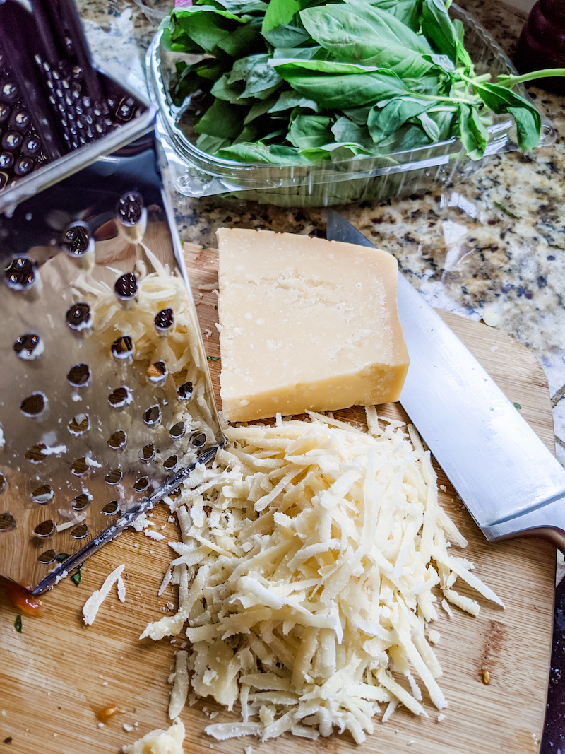 A pile of grated parmesan cheese next to a chunk of it and a grater.