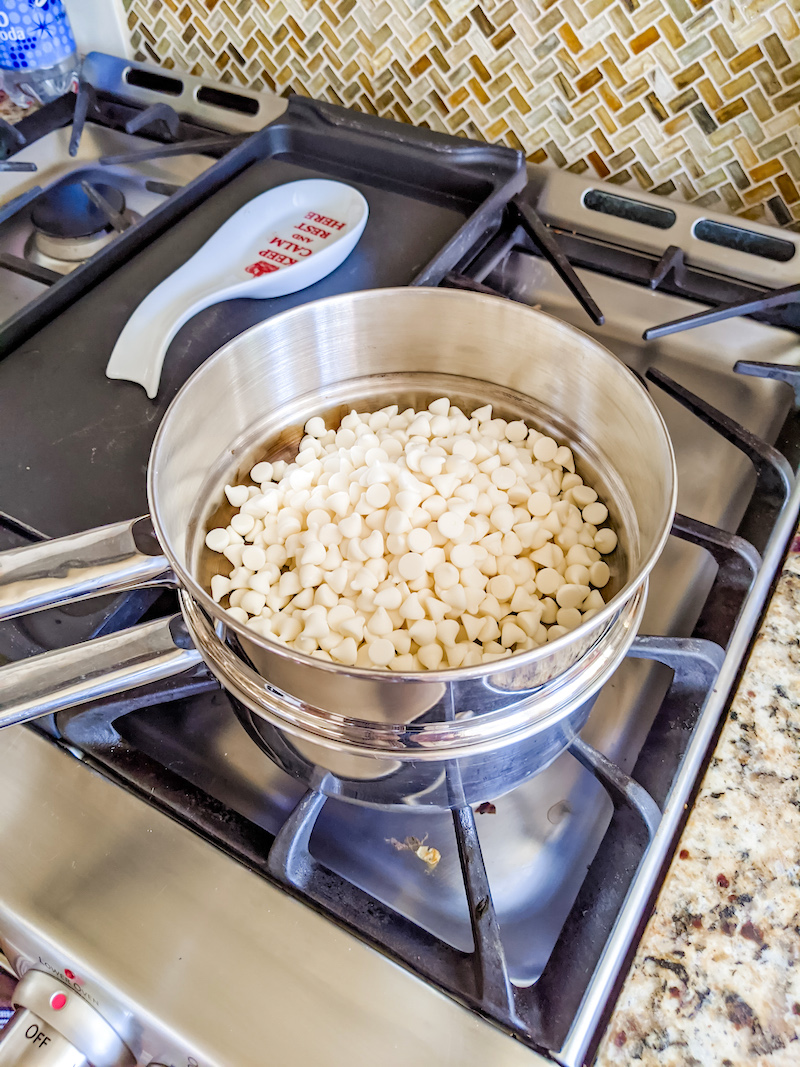 A double boiler atop a stove top with white chocolate chips.