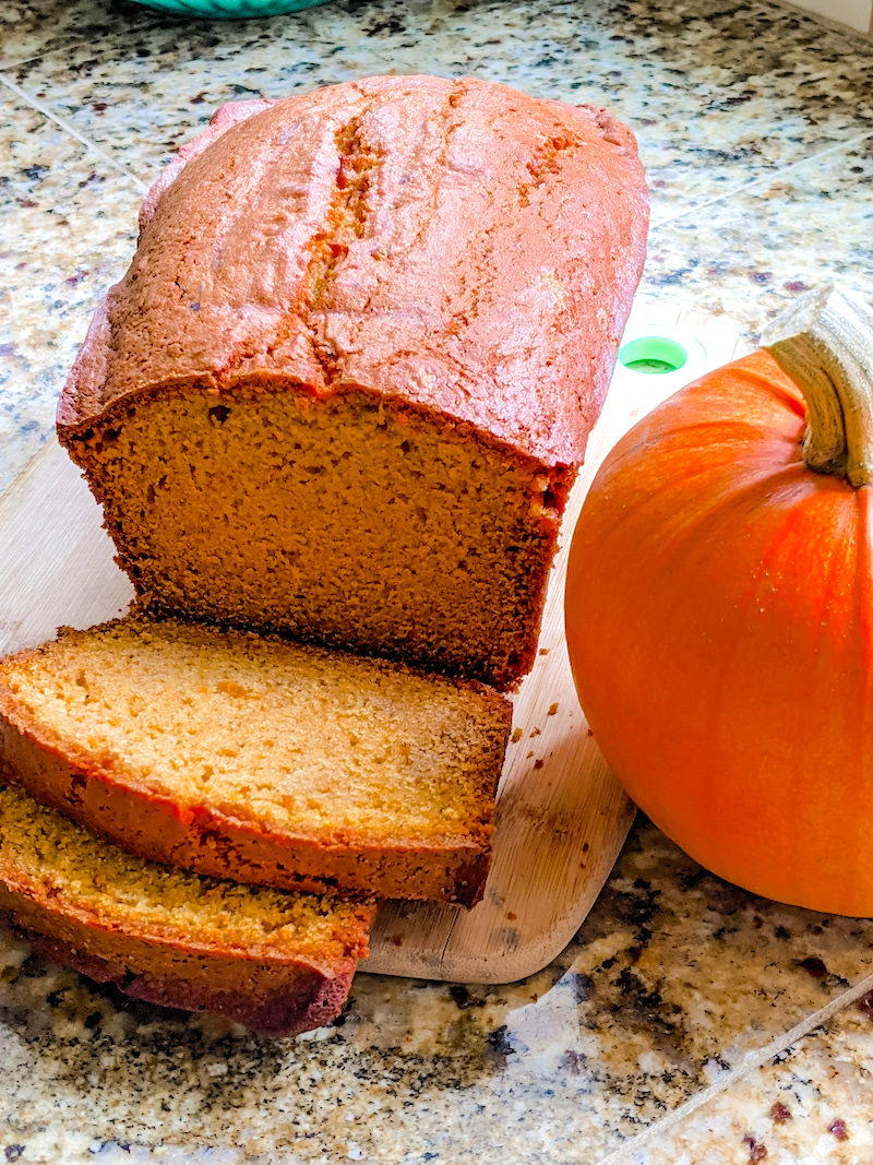 The Easy Homemade Pumpkin Puree used in a pumpkin bread, which sits, sliced, next to a pumpkin