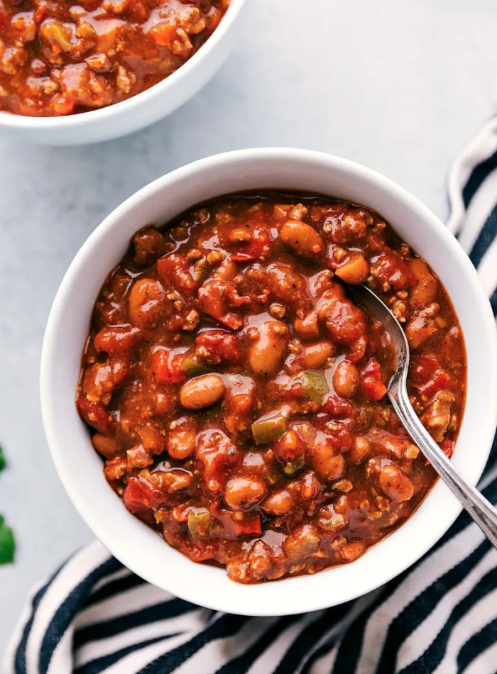 A serving of chili in a bowl, with a spoon in it