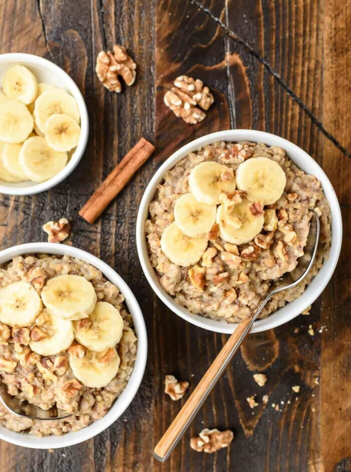 Several bowls of overnight oats with cinnamon sticks and slices of banana