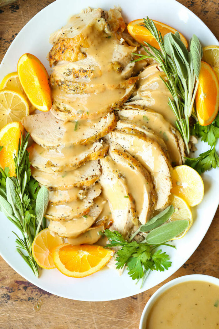 A serving dish with the turkey topped with gravy alongside herbs an oranges