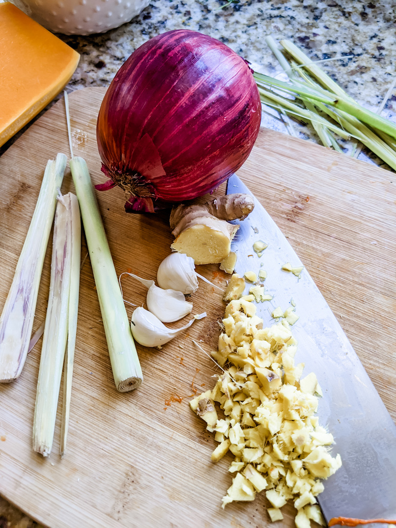 The ingredients for the slow cooker Thai Butternut Squash Soup, lemongrass, garlic, and an onion