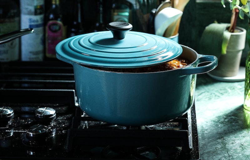 A photo of a crockpot with the lid slightly ajar on top of a stove top