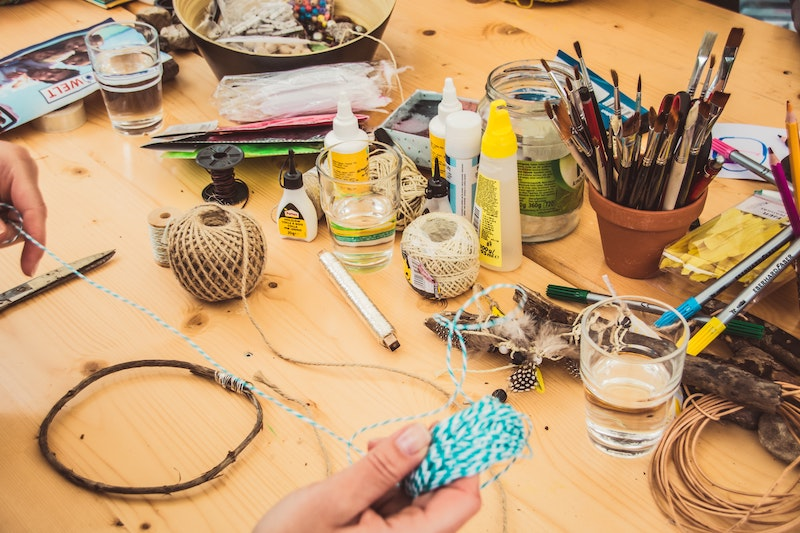 One of the things to do to stop worrying - a pair of hands above a table laden with crafting supplies (paints, brushes, yarn).