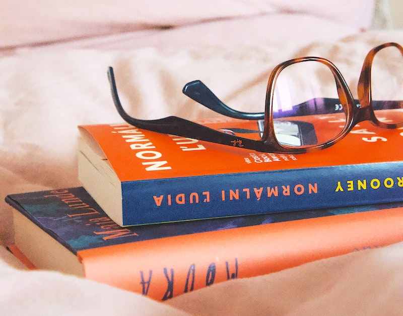 A stack of two books on a bed with glasses set upon them