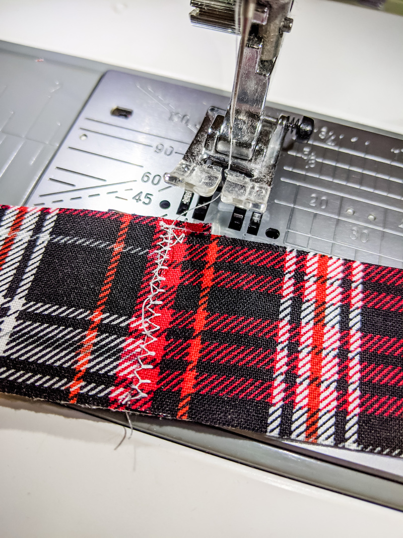 Sewing a zig zag across two strips of fabric using a sewing machine.