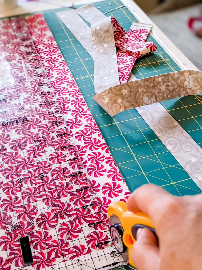 A rotary cutter cutting out measured strips of fabric