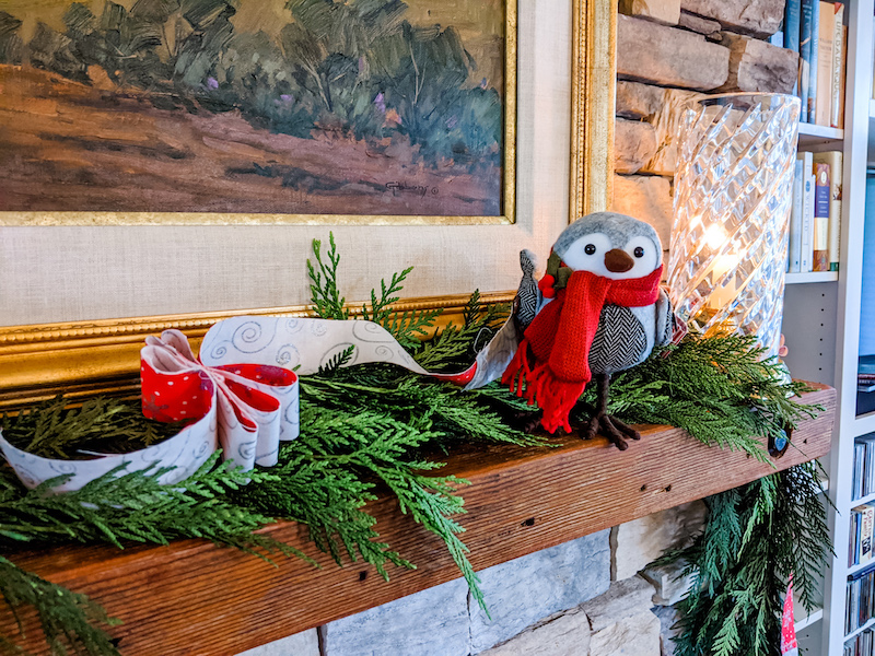 The DIY Christmas Garland on a mantle piece along with a bird knick knack and evergreen garland