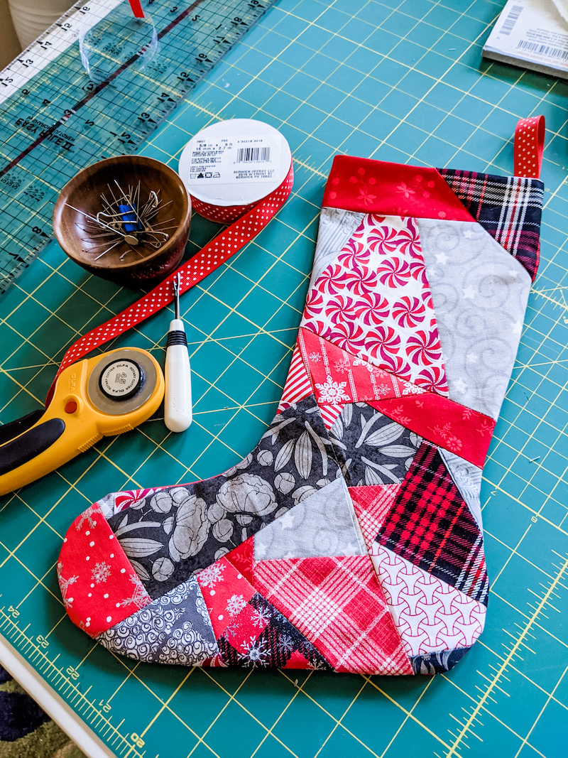 A finished Easy Patchwork DIY Christmas Stockings surrounded by the tools used to make it.