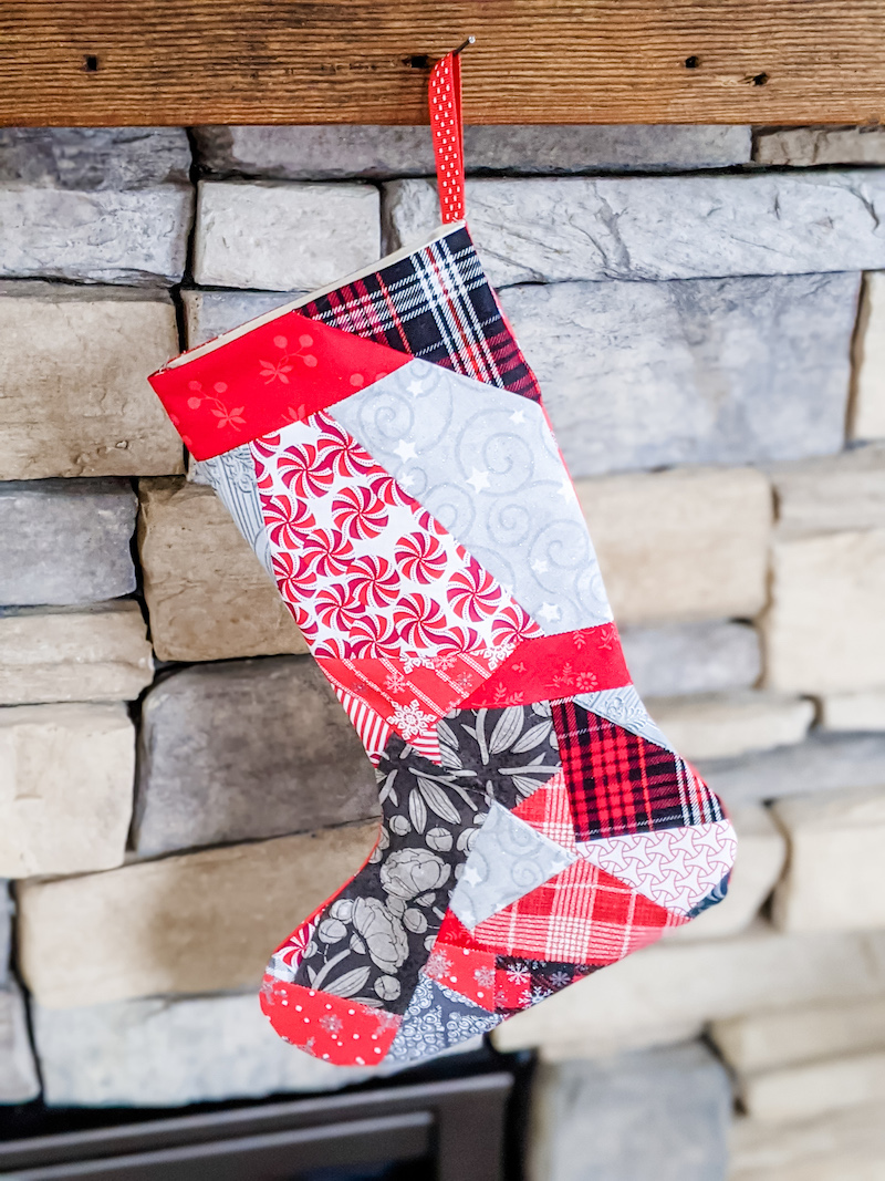 The Easy Patchwork DIY Christmas Stockings hanging on a stone fireplace