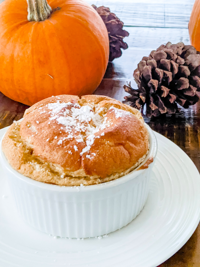 The finished Pumpkin Soufflé with Bourbon Molasses Sauce sitting on a table in front of a pumpkin and pinecone