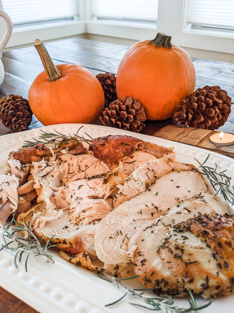The finished and sliced small scale oven roasted turkey breast on a platter with a pumpkin centerpiece behind