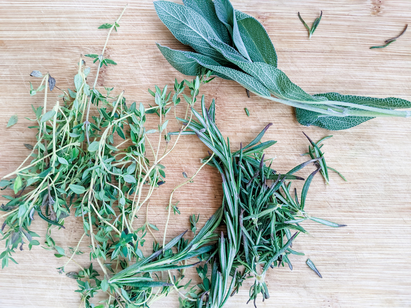Sprigs of fresh rosemary, sage, and thyme on a wooden board