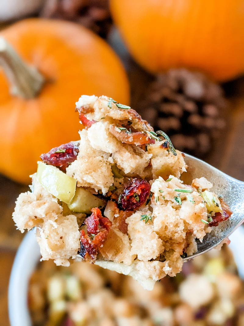 A spoonful of Marie's Flavorful and Moist Turkey Dressing, with a pumpkin and pine cone in the background