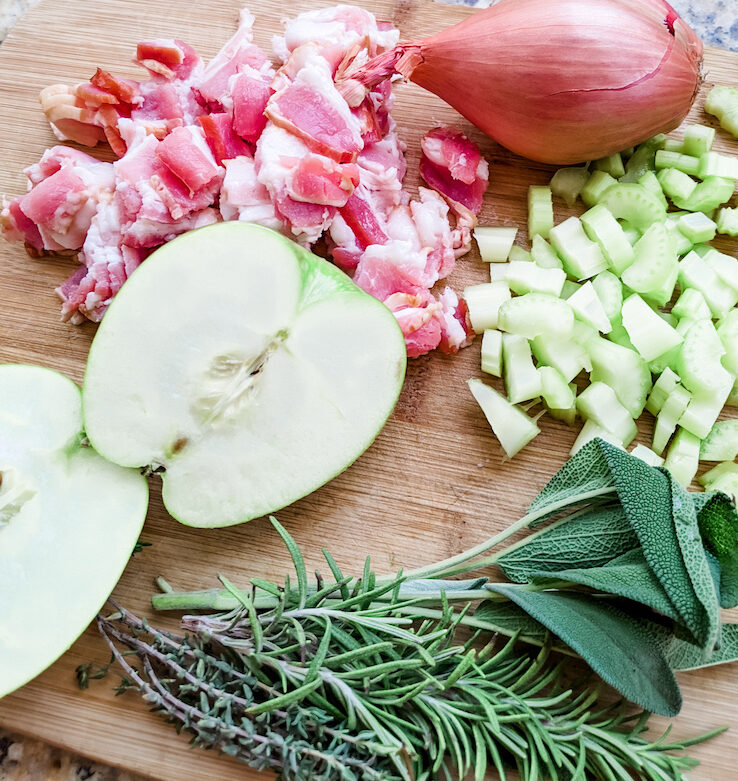 The ingredients for the best flavorful and moist turkey dressing - apple, bacon, herbs, shallots - on a cutting board