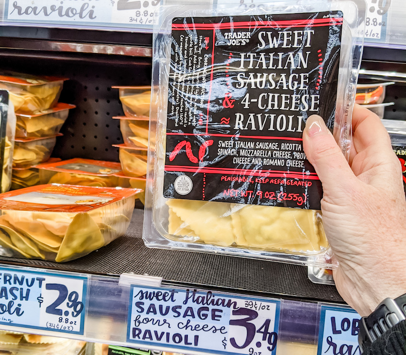 A hand pulling a package of fresh ravioli off a shelf.