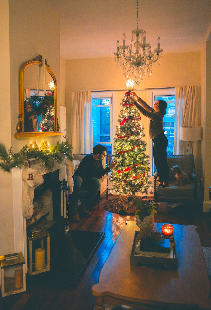 Celebrate Christmas from Home - a couple decorates their house and tree.