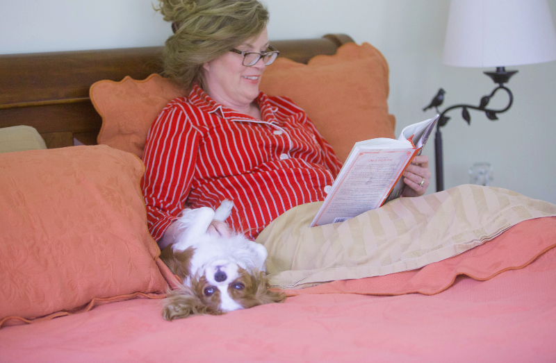 Marie sitting in bed alongside her dog, reading a book.