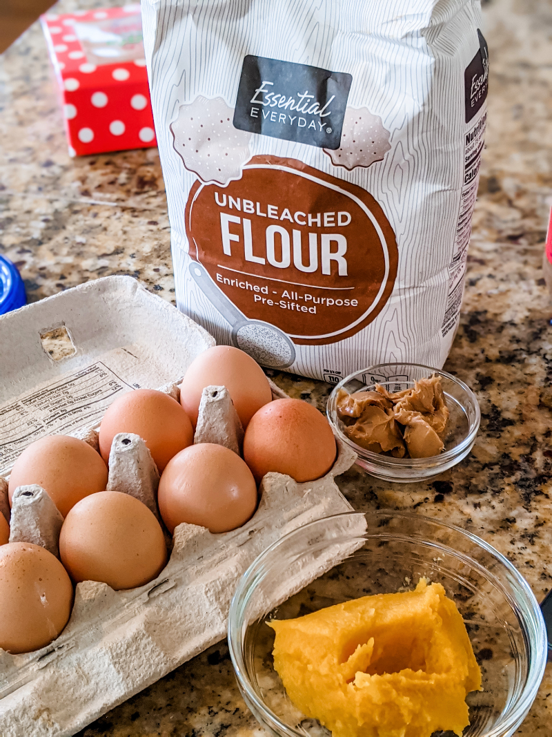 The ingredients for the dog treat recipe laid out - eggs, flour, pumpkin, and peanut butter.