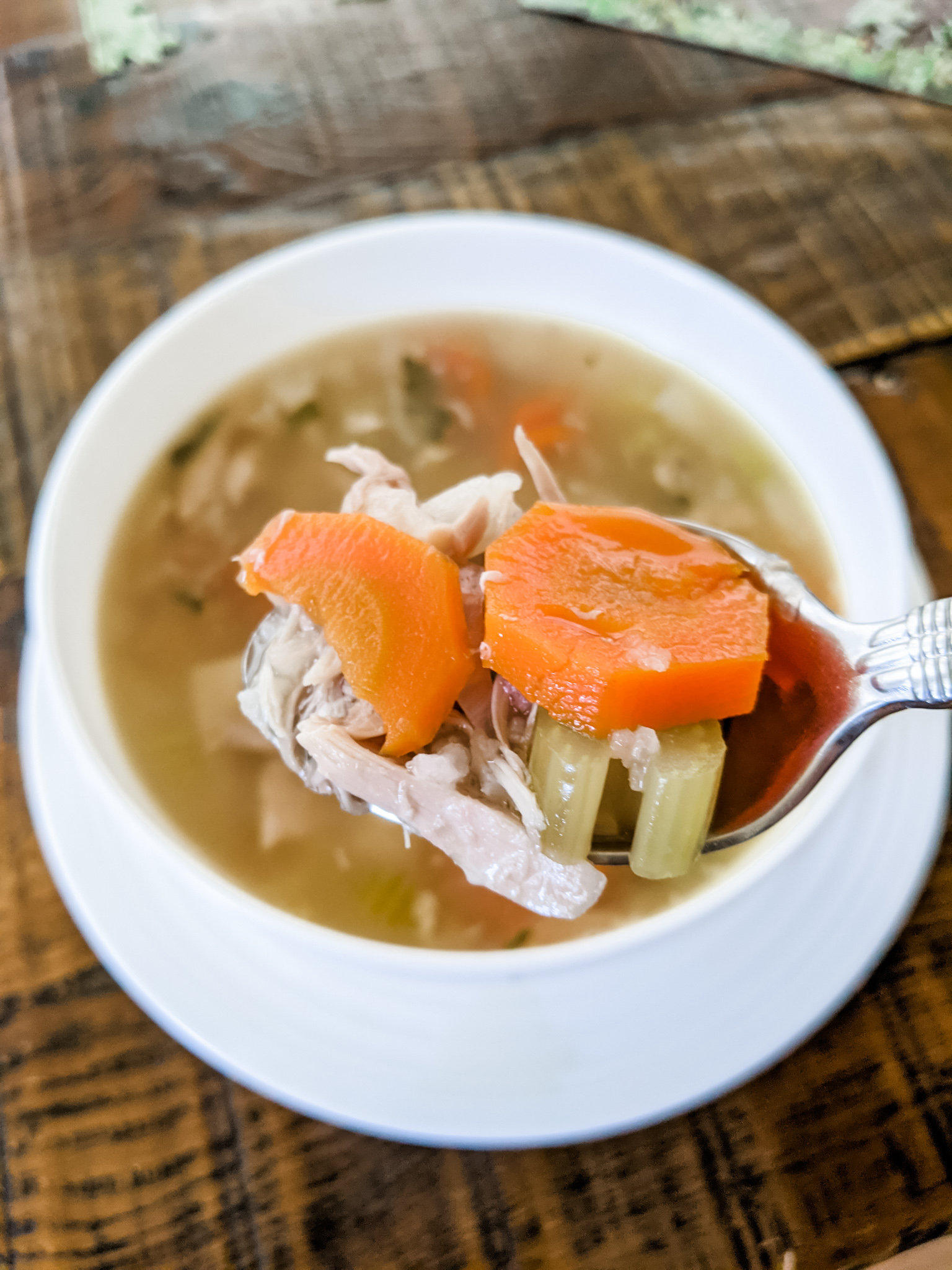 A bowl of the Leftover Turkey Soup Recipe with a spoonful being lifted out
