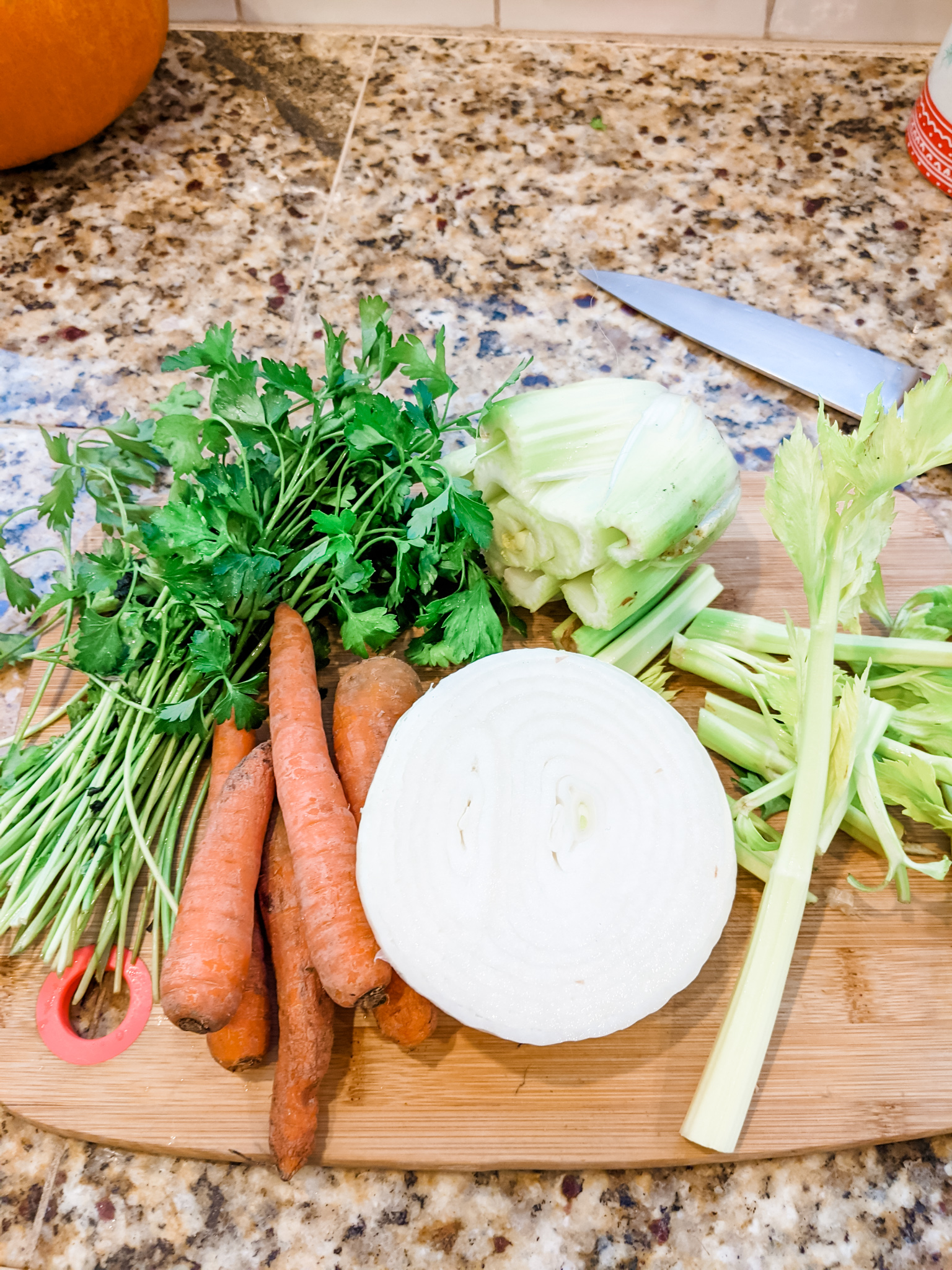 The veggies and scraps for the stock sitting on a wooden cutting board