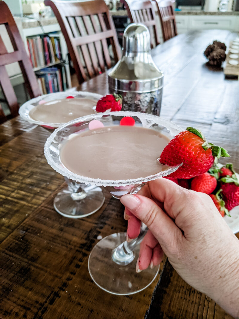 Marie holding one of the Chocolate Martini Cocktail, garnished with strawberries